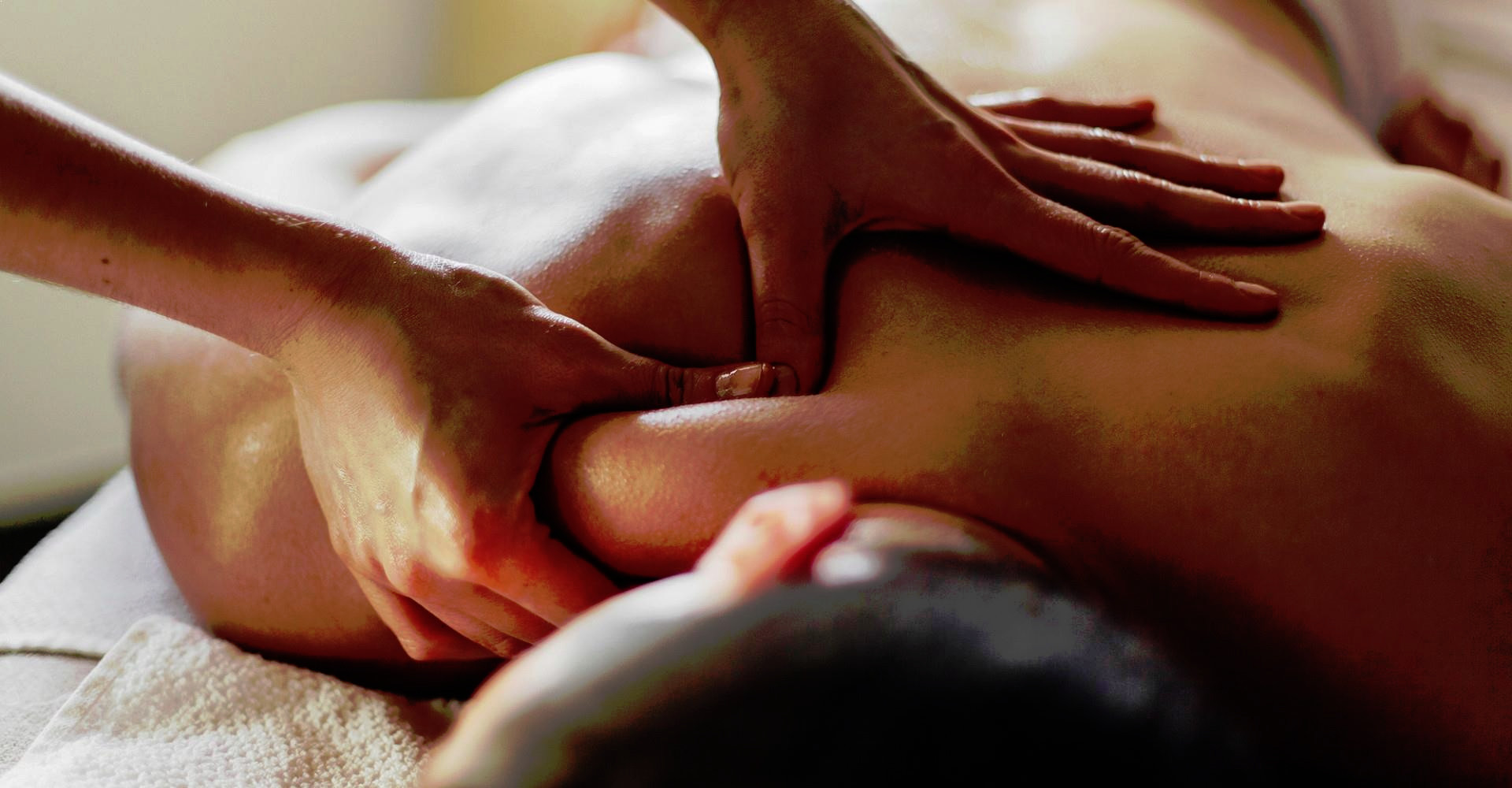 Close-up of masseur's hands massaging a client's back